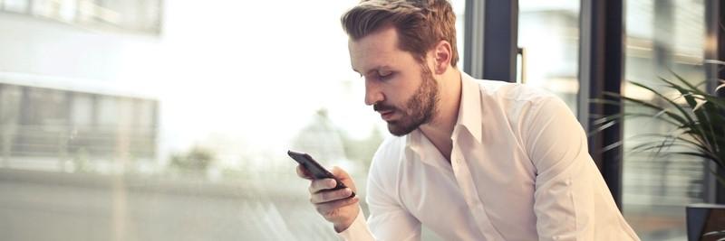 Mann schaut auf sein Handy - Kostenloses Aktiendepot