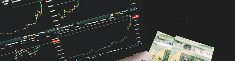 Euro Geldscheine liegen neben einem Laptop, auf dem Aktienkurse zu sehen sind. Lombardkredit