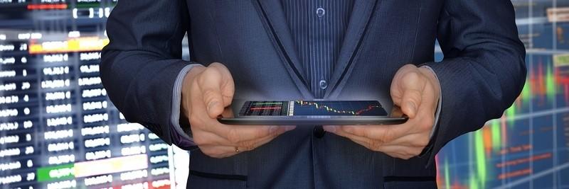 Mann im dunkelblauen Anzug hält mit beiden Händen ein Tablet, auf dem ein Chart zu sehen ist