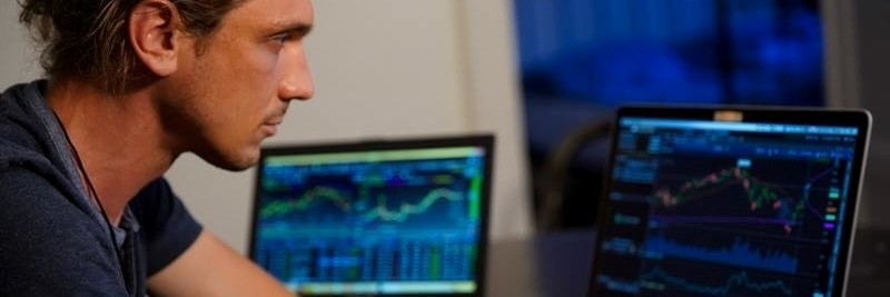 Mann sitzt vor Computer - Optionsscheinhandel