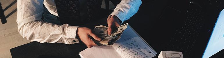 Mann zählt Geld am Schreibtisch