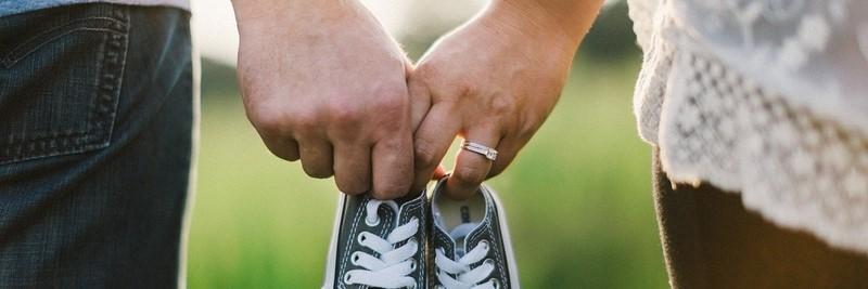 Ehepaar hält Händchen und hat Babyschuhe in der Hand