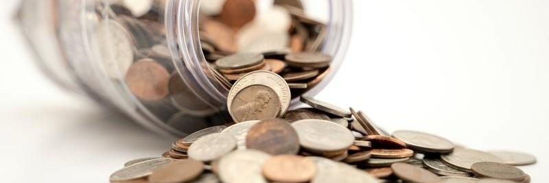 Geldmünzen fallen aus Glas / Spardose - p2p Plattformen Vergleich