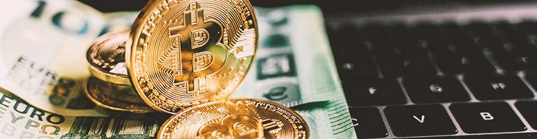 Bitcoin Münze und Euro Scheine liegen auf Laptop