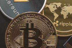 Krypto Münzen Bitcoin, Ripple und Ethereum liegen aufeinander